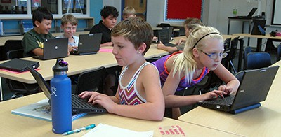 Students completing reading and writing assignments online