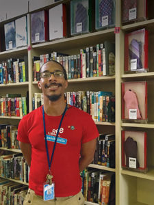 "Library assistant Omelio Alexander stands next to the ""tiebrary"" collection at the Paschalville branch of the Free Library of Philadelphia."