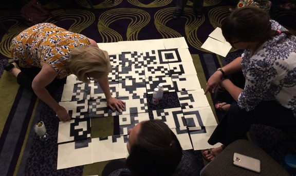 Attendees at the Gaming As Meaningful Education conference, cosponsored by the American Association of School Librarians and the American Library Association's Games & Gaming Round Table, solve puzzles in an escape room challenge.