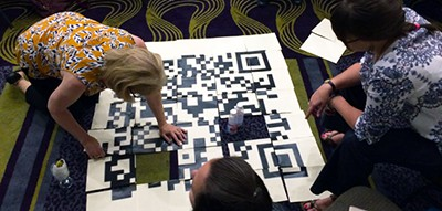 Attendees at the Gaming As Meaningful Education conference, cosponsored by the American Association of School Librarians and the American Library Association's Games & Gaming Round Table, solve puzzles in an escape room challenge