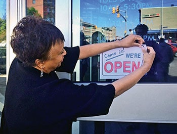 Hayden hangs a sign in the window of the Enoch Pratt Free Library, where she was CEO during the unrest in Baltimore in April 2015.Courtesy Enoch Pratt Free Library