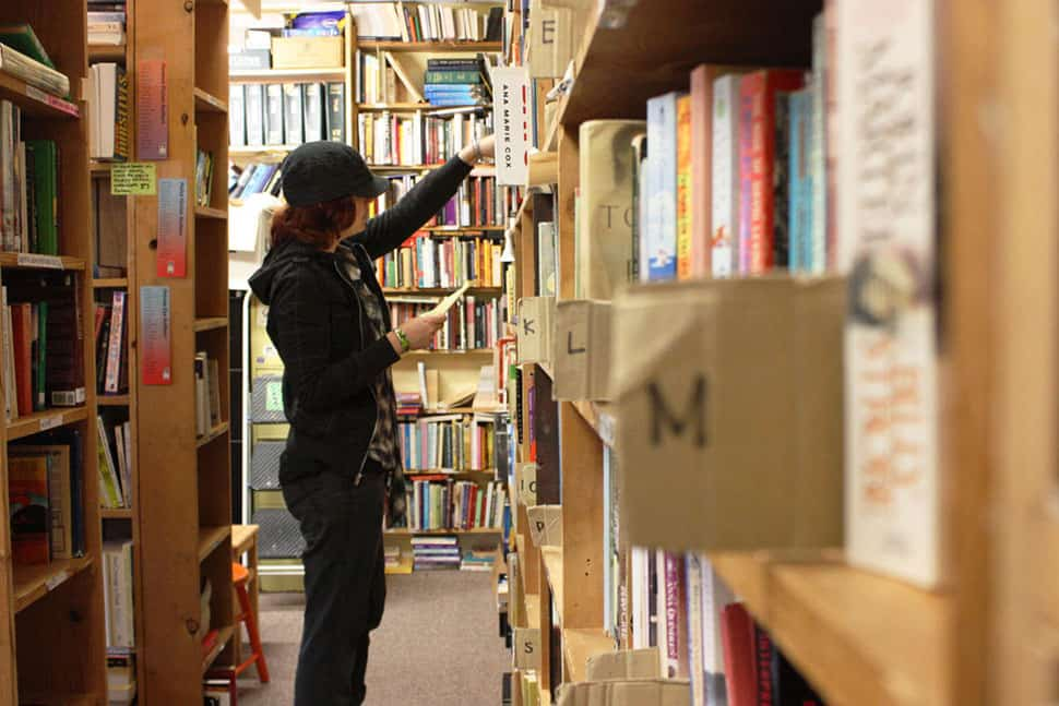 A volunteer with Books to Prisons Seattle searches the donated books to fulfill prisoner requests.