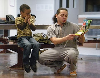 An inmate reads to his son at the Daddy and Me program's family day event, facilitated at a jail by Brooklyn (N.Y.) Public Library. (Photo: Brooklyn Public Library)
