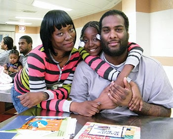 A family poses at the Daddy and Me program's family day event, facilitated at a jail by Brooklyn (N.Y.) Public Library. (Photo: Brooklyn Public Library)