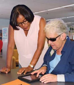 Assistive Technology Specialist Lolly Cheatham, left, trains a patron on the iPad through a New Jersey State Library program for veterans.