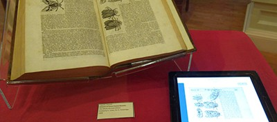Edward Topsell's History of Four Footed Beasts and Serpents (1658) on display at the 2015 Othmer Library Open House. An iPad next to the book displays a GIF made from one of the book's illustrations