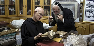 Father Columba Stewart inspects an ancient manuscript as a Syriac monk looks on at St. Mark's Syrian Orthodox Monastery in Jerusalem. Photo by Matilde Gattoni