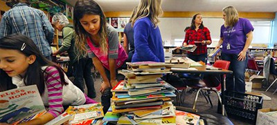 Librarians Kate Eads, second from right, and Kristine McLane, right, along with volunteers, sort books at North Beach Elementary for the libraries at Mary's Place. Photo by Alan Berner / The Seattle Times