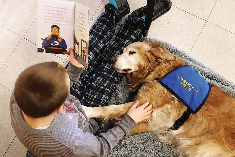 A Bedford, Indiana, student reads on pajama day at school to Bridget, a therapy dog owned by Mary Hall of Bedford Public Library. Photo: Mary Hall/Bedford (Ind.) Public Library