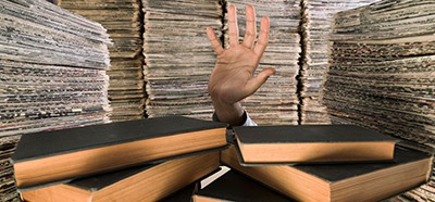Hand surrounded by books and papers