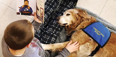 A Bedford, Indiana, student reads on pajama day at school to Bridget, a therapy dog owned by Mary Hall of Bedford Public Library