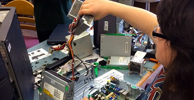 """Student working at the aptly named """"take-apart"""" station at the Makerspace at New Milford (N.J.) High School"""