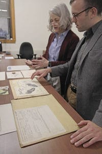 Martha Briggs (head of the Newberry's modern manuscripts division) and Alex Teller (director of communications) examine one of the job folders the company created when making its postcards.