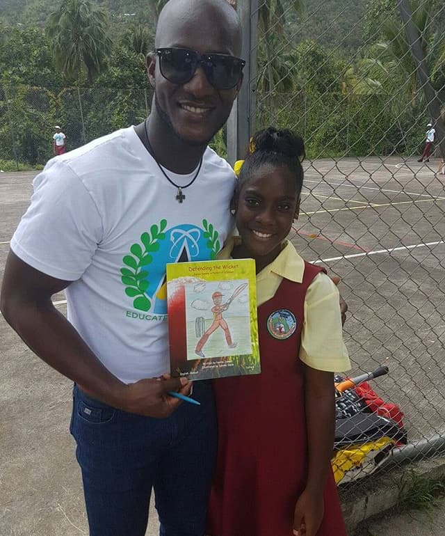 Daren Sammy (left), captain of the West Indies cricket team, with Soufriere Young Author Naima Joseph and her book about him.