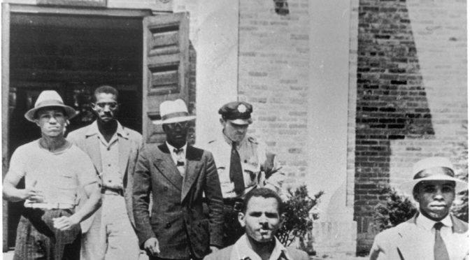 An officer escorts five men from the Alexandria (Va.) Library in August 1939. They were arrested and charged with disorderly conduct.