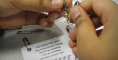 "The library circulation desk at Oliver McCracken Middle School in Skokie, Illinois, offers ""No Room for Hate"" pins assembled by the Social Justice Club that demonstrate a wearer's pledge to stand up against injustice. Photo by Tori Gammeri"