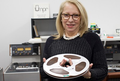 RAD Chief Laura Soto-Barra holding a reel-to-reel tape in the NPR RAD digitization lab. (Photo: Wanyu Zhang/NPR)