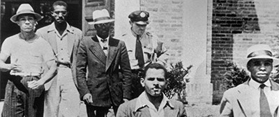 An officer escorts five men from the Alexandria (Va.) Library in August 1939. They were arrested and charged with disorderly conduct