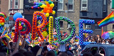 Image of Pride marchers holding ballons spelling PRIDE