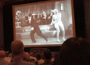 Audience members view a clip from the RKO film Peach O' Reno with Bert Wheeler and Dorothy Lee.