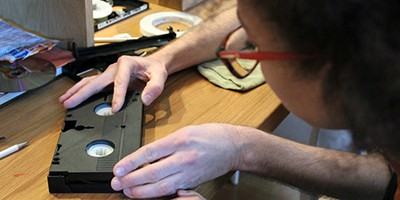 XFR Collective member Carmel Curtis works on a VHS cartridge during an event at the Baltimore Museum of Art in March