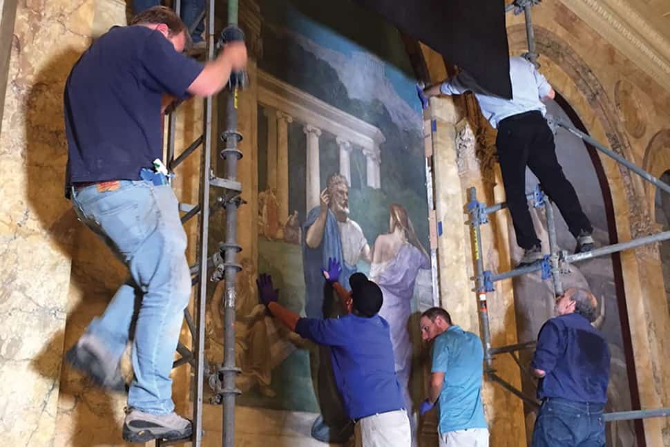A team returns a restored mural to the wall in Boston Public Library's Bates Hall.