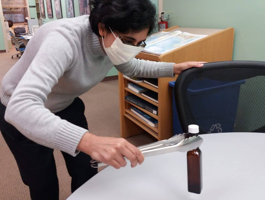 "Avon Lake Public Library gave one of its A1 Sauce bottles to Dewey Decibel for ""further analysis."" Here, American Libraries Managing Editor Sanhita SinhaRoy lends her eye to the investigation. Photo: Terra Dankowski/American Libraries"