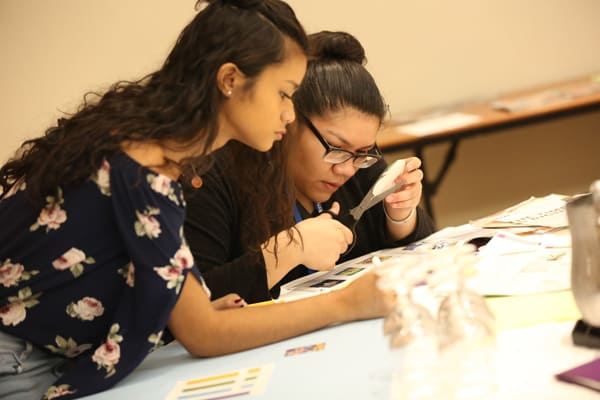 Interns Nika Cunanan from Waipahu (Hawaii) Public Library (left) and Samantha Martinez from Anythink Libraries (Adams County, Colo.) work together on a project at the commencement event in Chicago on October 14. (Photo: Tori Soper)
