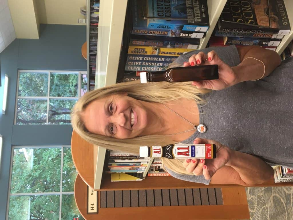 Vicki George, circulation specialist at Avon Lake Public Library, found one of two suspected copycat bottles. The A1 Sauce bottle that she found was full and still had its label. Attached to her bottle was an envelope containing a handwritten poem. Photo: Courtesy of Avon Lake Public Library
