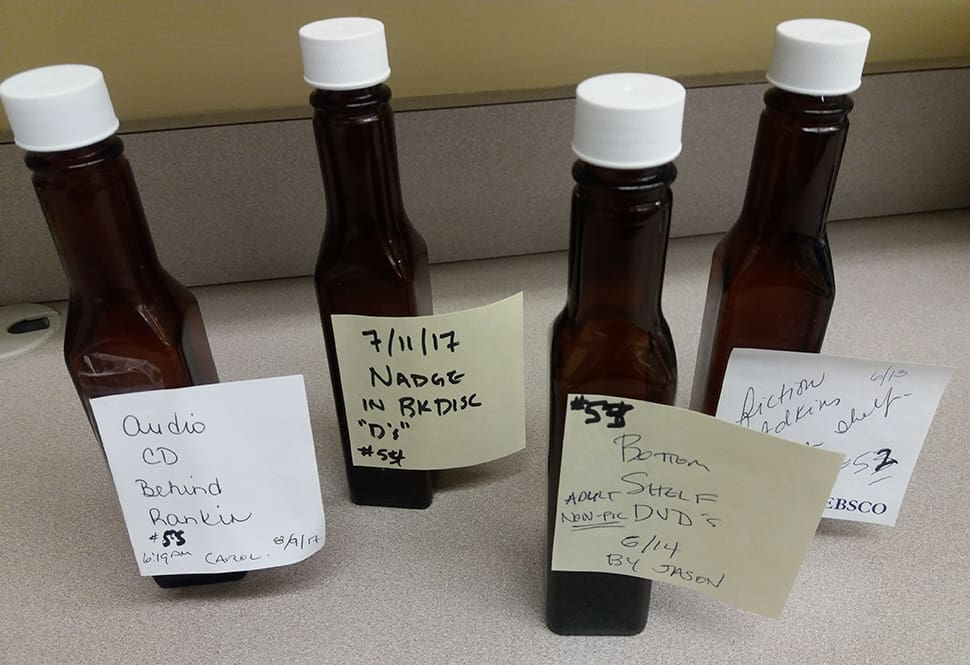 A few of the emptied, cleaned, and delabeled A1 Sauce bottles that were found in the stacks were flagged with Post-it notes indicating which library employee found the bottle, and when and where the bottle was found. Photo: Terra Dankowski/American Libraries