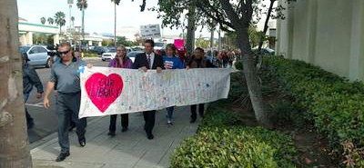 About 50 people marched from the Escondido Public Library to City Hall November 28 to deliver a copy of a lawsuit that challenges a decision to outsource the library's management and staff. Photo by J. Harry Jones / Union-Tribune