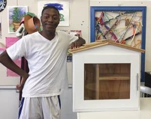 "Artist Wayne Pace poses next to a Little Free Library before painting it as part of the Little Library Prize competition at the 2017 Michigan State Fair. <span class=""credit"">Photo: Detroit Little Libraries</span>"