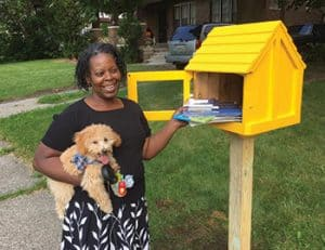 Kathy Henderson stands next to a Little Free Library in Highland Park, Michigan. Photo: Detroit Little Libraries