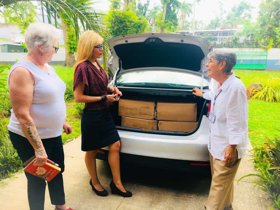 ALA President-Elect Loida Garcia-Febo (center) brings boxes of books donated by Lectorum to San Juan Community Library.