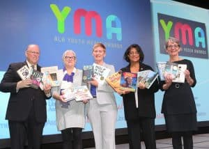 At the Youth Media Awards, from left: ALA President Jim Neal, Reforma President Tess Tobin, Association of Library Service to Children President Nina Lindsay, Coretta Scott King Chair Claudette McLinn, and Young Adult Library Services Association President Sandra Hughes Hassell display the winning books.