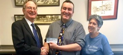 Seymour Town Supervisor Jerry Underwood presents his salary check to Seymour Library Director Carl Gouveia and Library Board President Taysie Pennington