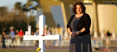 Diana Haneski, a librarian at Marjory Stoneman Douglas High School, poses for a portrait near one of the crosses erected for the victims of the school shooting in Parkland, Florida. Photo by Reuters/Jonathan Drake