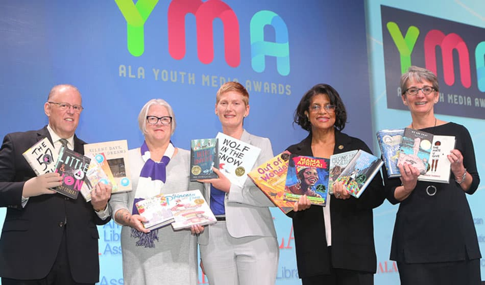 "At the Youth Media Awards, from left: ALA President Jim Neal, Reforma President Tess Tobin, Association of Library Service to Children President Nina Lindsay, Coretta Scott King Awards Chair Claudette McLinn, and Young Adult Library Services Association President Sandra Hughes-Hassell display the winning books. <span class=""credit"">Photo: Cognotes</span>"