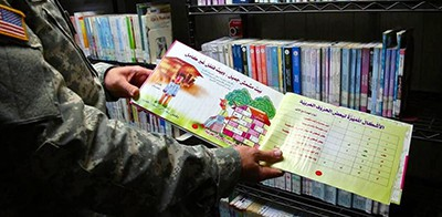 A soldier showed a photographer a child's book in the Detainee Library at Guantánamo on Nov. 4, 2014. Captives with borrowing privileges don't browse the stacks. The military delivers a selection to the captives, who can also request a title to find out if it is in the collection. Photo by Miami Herald