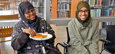 Ruqia Abdi, Hennepin County Library Cultural Liaison (left), visits with a Cedar Riverside volunteer ambassador (right) at the East Lake Library Welcome Event. Abdi's role as a cultural liaison was key to the outreach project's success