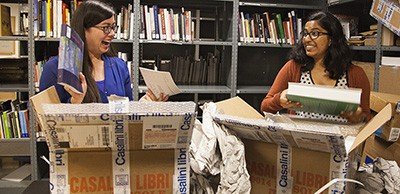 Marie Faye Barrera and Linta Kunnathuparambil unpack newly acquired titles for the Getty Trust Library