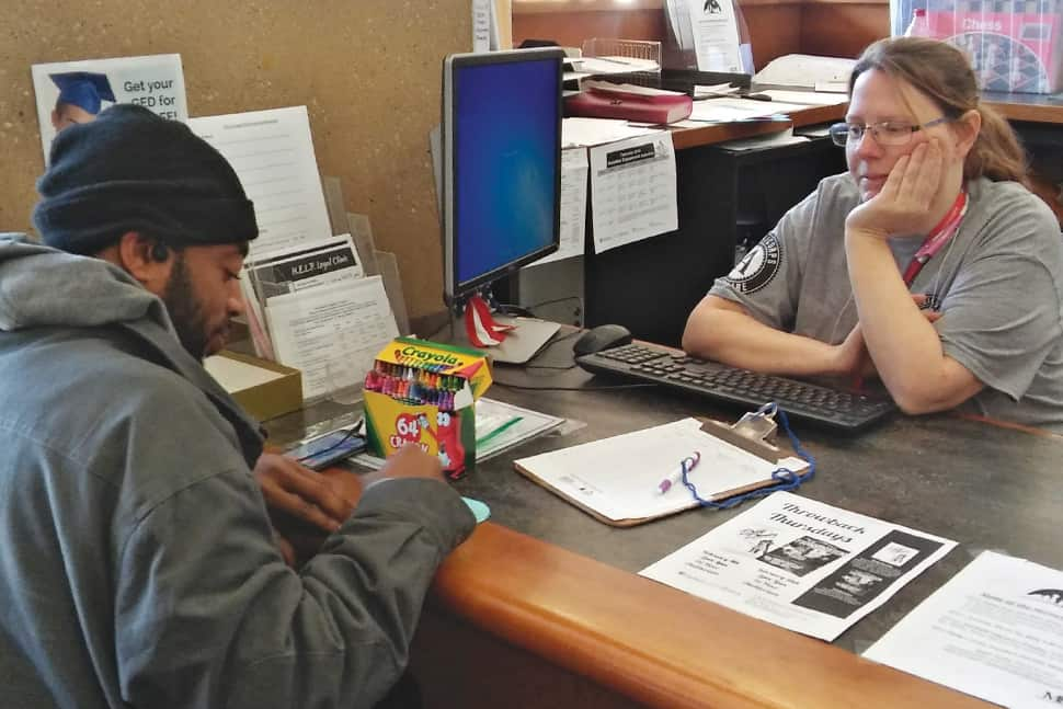Dallas Public Library Youth Services Administrator Melissa Dease assists a homeless patron during the annual Winter Backpack Challenge, part of the library's Homeless Engagement and Leadership program. Photo: Dallas Public Library