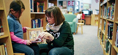 "Gonzales Community School librarian Kelly McCabe helps Olvia Santos, 6, find a book to read. McCabe says for students, library time ""gives them choice and the chance to explore things that they are interested in."" Photo by Craig Fritz / The New Mexican"