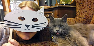 Page Turner, Bristol (Ind.) Public Library's cat, poses with a person holding a cat mask at the library