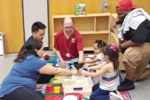 Drew Alvey (in red shirt), manager of Houston Public Library's Stimley–Blue Ridge branch, models interactive play for families. Photo: Houston Public Library