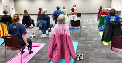 Jessica Humphrey demonstrates some chair yoga moves during a Beginners Yoga class at Mentor (Ohio) Library