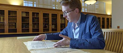 Rowan W. Dorin, assistant professor of history, with the miscataloged parchments whose mystery he is working to solve. Photo by L. A. Cicero