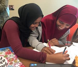 Ayan Ismail (left) and Hikmo Abdi, 10th graders at Roosevelt High School in Minneapolis, work on geometry homework at Hennepin County Library's Roosevelt Library.