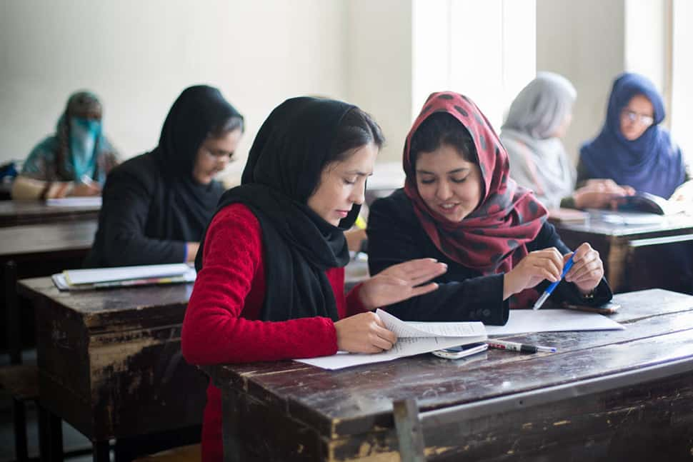 Students at a teacher's college in Parwan Province, Afghanistan, learn about the Darakht-e Danesh Library.