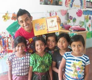 Salvador Isaías Sisay Tuch, coordinator of programs for La Biblioteca Móvil, poses with children served by the traveling library.